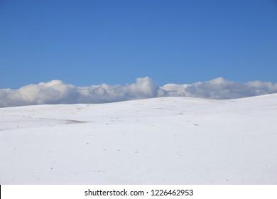 neutral winter landscape. Snow slope, horizon, clouds