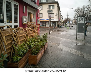 NEUWIED, GERMANY - Feb 06, 2021: empty streets and stacked chairs in front of a pub on a rainy day in the second lockdown based on the Corona pandemic
