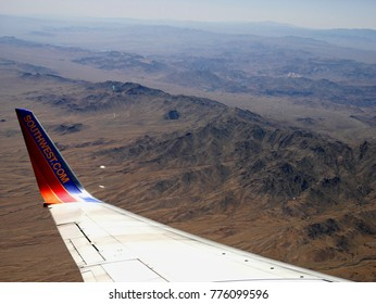 NEVADA, USA—APRIL 2017: Aerial view of dry rocky mountains heading to Nevada with the wing tip of a Southwest Airlines aircraft seen from the airplane window.
