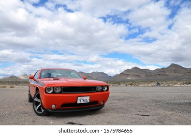 Nevada, USA - 02.10.14: Dodge Challenger Fast red orange sport muscle car  in cloudy weather near mountains in desert
