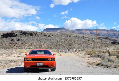 Nevada, USA - 02.10.14: Dodge Challenger Fast red orange sport muscle car with burning lights in cloudy weather near mountains