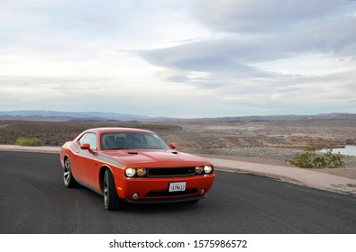 Nevada, USA - 02.10.14: Dodge Challenger Fast red orange sport muscle car with burning lights in cloudy weather