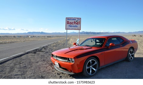 Nevada, USA - 02.10.14: Fast red orange sport muscle car Dodge Challenger in desert near straight as an arrow road, Rhachel city, zone 51