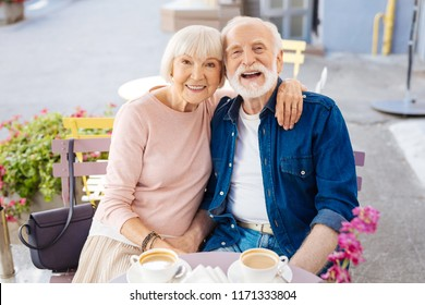 Never boring. Smiling senior couple sitting at cafe and looking at camera