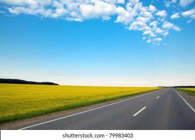 緑の野原と青く曇った空を通る幹線道路は絶えず終わる