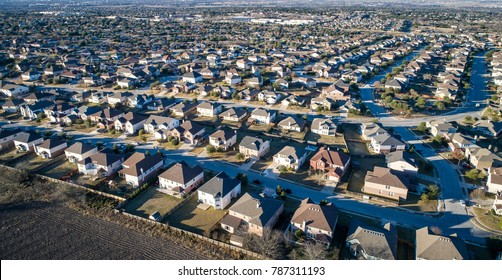 Never ending houses and rooftops as housing market development grows in Endless homes in suburb aerial drone view from above suburbia. Rooftops and square little boxes