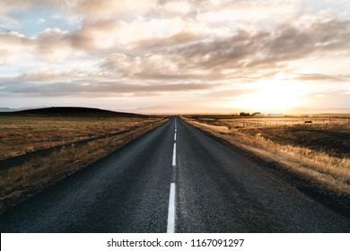 Endlos Straße bis zum Horizont auf Sonnenaufgang