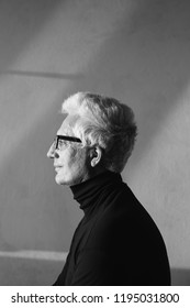 Never get old, handsome and sexy at every age concept. Profile portrait of fashionable mature man wearing trendy eyewear, black turtleneck. Modern haircut. Silver hair. Daylight. Graphic shadows