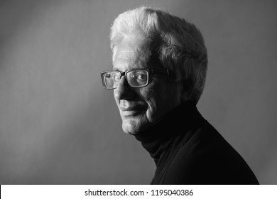 Never get old, handsome and sexy at every age concept. Close up portrait of fashionable mature man wearing trendy eyewear, black turtleneck. Modern haircut. Silver hair. Daylight. Graphic shadows
