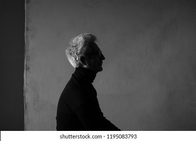 Never get old, handsome and sexy at every age concept. Portrait of fashionable mature man wearing trendy eyewear, black turtleneck, sitting in art gallery. Modern haircut. Silver hair. Graphic shadows