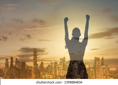 Never give up concept. Strong young confident woman with fist up to the sky against city background. Double exposure