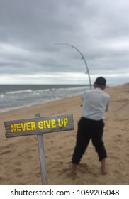 Never Give Up sign on beach background with fisherman struggling