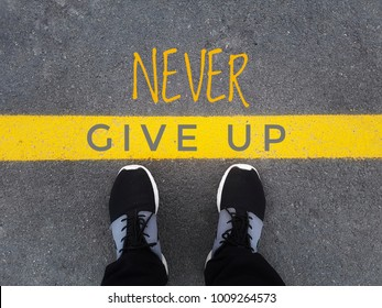Never Give up text  on asphalt ground, feet and shoes on floor