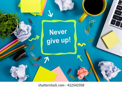 Never give up. Office table with notepad, computer and coffee cup on blue background. Business creative consept top view