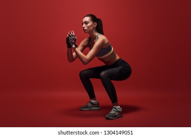Never give up. Sportswoman standing over red background, stretching her body