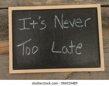 It's never too late written in chalk on a chalkboard on a rustic background