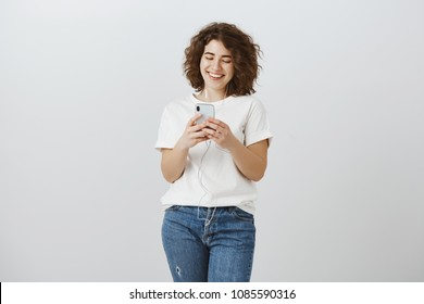 Never leave home without earphones and smartphone. Portrait of attractive curly-haired urban girlfriend, holding phone, laughing while looking at screen, messaging and listening music in earbuds