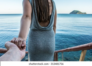 Never letting go, romantic couple holding hands at water