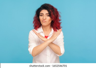 Never, no compromise! Portrait of dissatisfied hipster woman with fancy red hair crossing hands, showing x sign, ban or prohibition gesture, rejecting offer. studio shot isolated on blue background