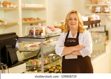 Never too old for business. Shot of a cheerful senior woman posing proudly near the showcase at her own bakery