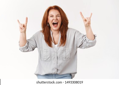 Never too old rock-n-roll. Daring cool redhead middle-aged woman having fun go wild scream out loud positive upbeat mood excited show heavy metal gesture listen loud music, white background