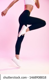 Never stop Cropped photo of sporty young woman in black leggings jumping against pink background in studio