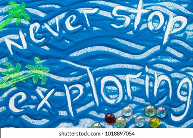 Never Stop Exploring inscription on a blue colored sand with waves and decorative palm trees, top view, flat lay