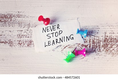 Never Stop Learning, handwriting quotation on peace of paper