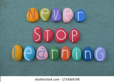 Never stop learning, motivational phrase composed with creative multi colored stone letters over green sand