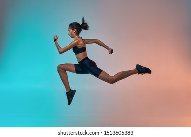 Never stop run! Full length of young athlete woman with perfect body in sports clothing jumping in studio against colorful background