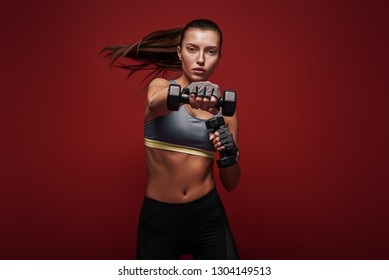 Never stop! Sportswoman is exercising with dumbbells standing over red background