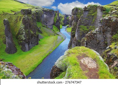 Neverland Iceland. The picturesque canyon Fjadrargljufur, green cliffs and blue water of the river