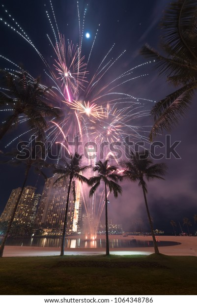 New Year's 2018 fireworks at the Hilton Hawaiian Village in Honolulu, Hawaii with the beach, palm trees and a lagoon