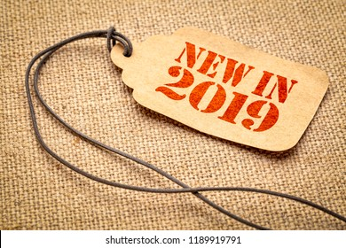 new in 2019 sign - a paper price tag with a twine against burlap canvas