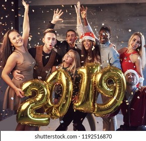 New 2019 Year is coming! Group of cheerful young multiethnic people in Santa hats carrying gold colored numbers and throwing confetti on the party.