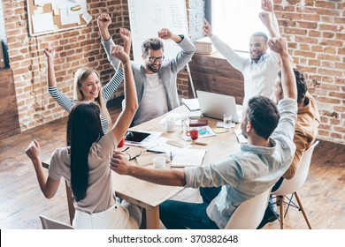 New achievement! Top view of group of six cheerful young people keeping arms outstretched and smile while sitting at the table in office