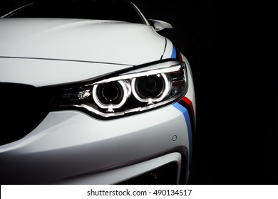 New aggressive headlight by night. Car details. The front lights of the sports car. Car's light. Insurance concept