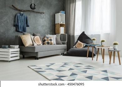 New apartment interior in grey with sofa, modern pouf, small table, two chairs and pattern carpet