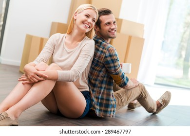 New apartment for living together. Smiling young couple sitting on the floor of their new apartment while cardboard boxes laying in the background
