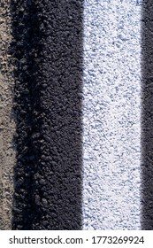 New asphalt road edge, closeup detail of black tarmac road edge and white line delimitation, top view background