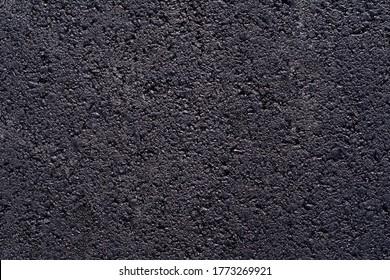 New asphalt road texture, closeup detail of black tarmac road, top view background of a grainy road