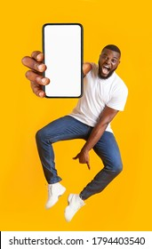 New awesome mobile app. Closeup of smartphone with blank screen in jumping emotional black guy hand, yellow studio background