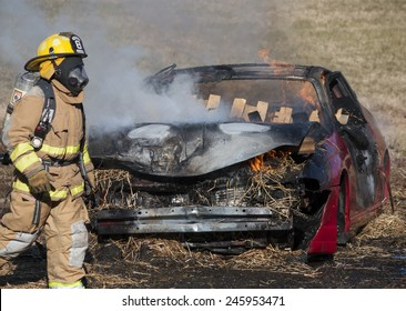 New Baltimore, Virginia, USA-January 17, 2015: Fireman training on a burning car at the New Baltimore Fire Station in New Baltimore, Virginia.