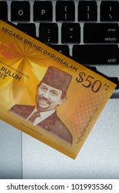 New banknote 50 year The Currency (Brunei currency) on laptop . 50 dollar banknote of Brunei with extremely closeup in security feature on polymer substrate and holograms in note, copy space