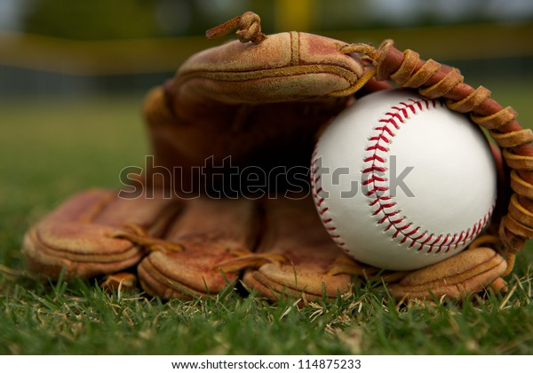 New Baseball in a Glove on the Outfield Grass