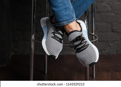 New beautiful colorful and nice Adidas Iniki running shoes, sneakers, trainers showing the logo with a brand box on abstract background. Sport and casual footwear concept. Kyiv, Ukraine-July 26, 2018
