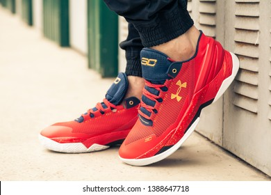 New beautiful colorful and nice Under Armour running shoes, sneakers, trainers shows a brand logo on abstract background. Sport and casual footwear concept. Kyiv, Ukraine-MAR 24, 2019