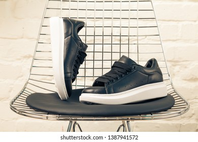 New beautiful Mc Queen running shoes, sneakers, trainers shows a brand logo on abstract background. Sport and casual footwear concept. Kyiv, Ukraine-MAR 16, 2019