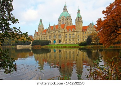 New beautiful mighty City Hall (German: Neues Rathaus) in Hanover, Germany, reflects in calm water of park pond with wild ducks on foggy autumn morning. Allegory of power and beauty. Architecture.