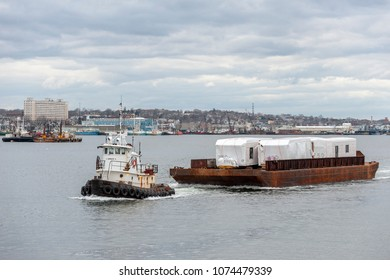 New Bedford, Massachusetts, USA - April 17, 2018: Tug Sirius towing barge load of modular homes across New Bedford harbor